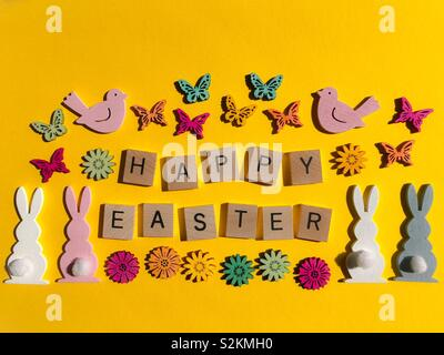 Happy Easter, in wooden letters with bunny rabbits, birds, flowers and butterflies - Stock Image