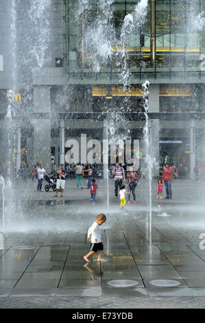 Child playing in water fountains in public open space near Cable Car station, Tung Chung, Lantau Island, Hong Kong, - Stock Image
