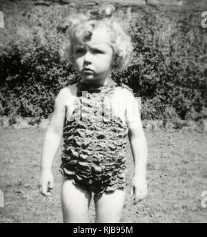 A little girl wearing a rather bizarre crimpled swimsuit - Stock Image