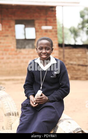 Young attractive ugandan school children, wearing smart uniforms, hold their cameras and look at the smiling - Stock Image