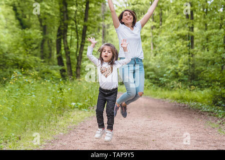 Young mom and little girl jump together together.Happy mother and daughter moments with love and natural emotion.Photo of young mother and her daughte - Stock Image