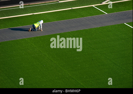 image of worker laying green astroturf surface on sports playing field - Stock Image