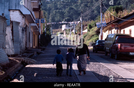 An indigenous Kiche Mayan woman walking home with her children, Momostenango Township, Guatemala. - Stock Image