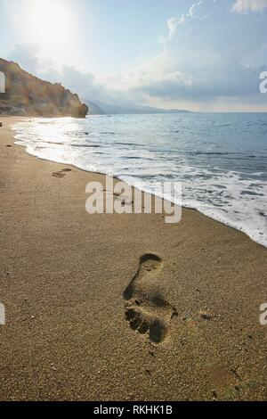 Footsteps in the wet sand at shore, Preveli beach, Rethymno, Crete, Greece - Stock Image