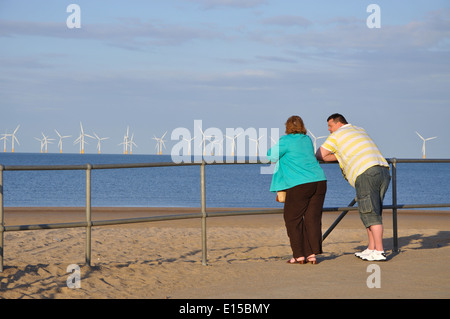 couple leaning on railings and looking out to sea, Skegness, Lincolnshire, England, UK - Stock Image
