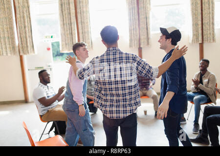 Men talking and clapping in group therapy in community center - Stock Image