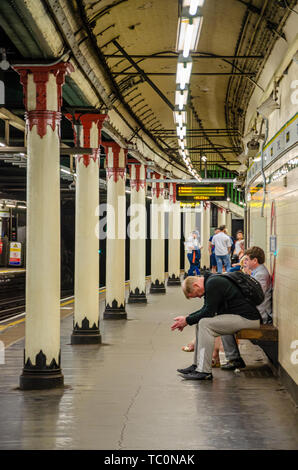 A man sits on a bench on the platform at Temple London Underground  station looking tired. - Stock Image