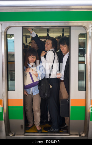 Workers crowded during rush hour onto a train in Tokyo Japan - Stock Image
