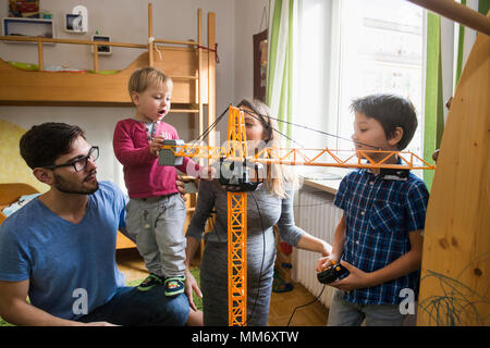 Two brothers and parents are playing with a toy crane, Munich, Germany - Stock Image