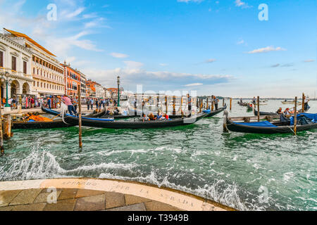 Tourists fill the gondolas at the Grand Canal station as visitors enjoy the Riva Degli Schiavoni shops and cafes along the promenade in Venice Italy - Stock Image