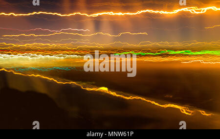 A long exposure from a moving plane transforms airport lights into streaks of colour. - Stock Image