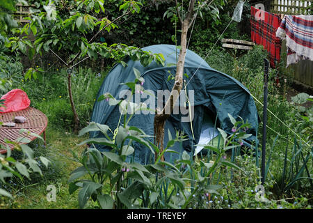 A tent set-up in a very small garden. - Stock Image