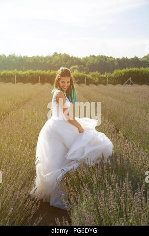 Beautiful bride in wedding dress outdoor in a field at sunset - Stock Image