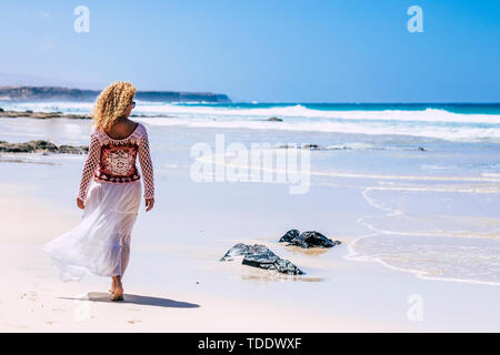 fashion trendy blonde curly woman walking on the white sand tropical resort beach with blue ocean in background - travel and summer holiday concept fo - Stock Image