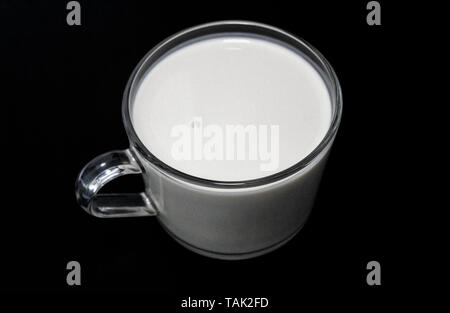Cup with yogurt on a black table - Stock Image