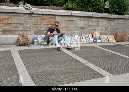 A young male artist painting and selling his work at Union Square PArk in Manhattan, New York City. - Stock Image