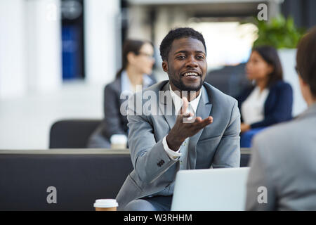 Positive confident handsome young black bearded businessman in gray suit sitting in lobby and gesturing hand while talking to business partner during - Stock Image