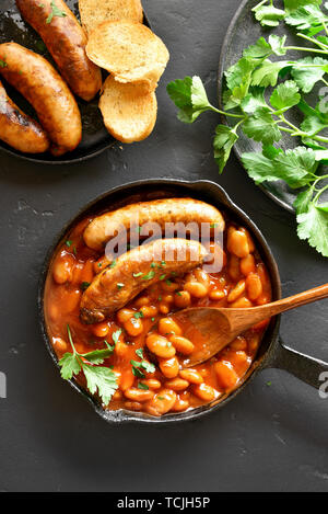 Grilled sausages with baked white beans in tomato sauce in frying pan over black stone background. Top view, flat lay - Stock Image