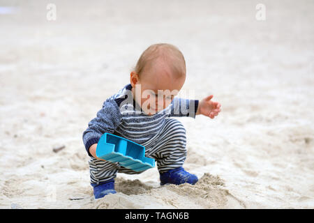 Cute Baby Boy Playing With Sand And Blue Plastic Shovel On The Sea Beach - Stock Image