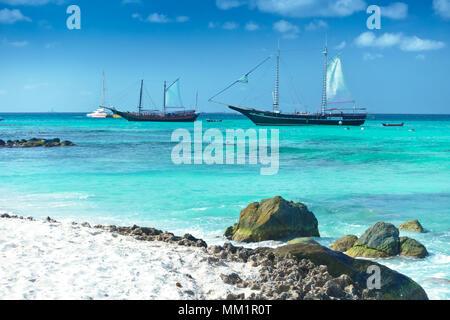Arashi Beach, Aruba, Caribbean Sea in January 2018: 2 tour boats anchored for tourists to go swimming or snorkeling. - Stock Image