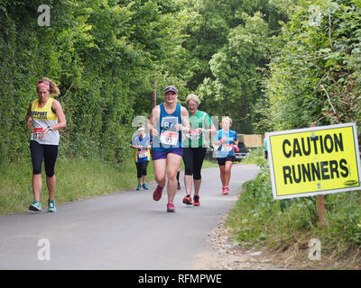 Female runners taking part in a ladies road running race with a 'caution runners' sign on the road - Stock Image