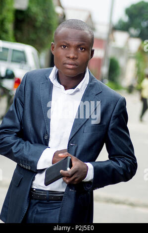 young african businessman taking something in the pocket of his jacket. - Stock Image