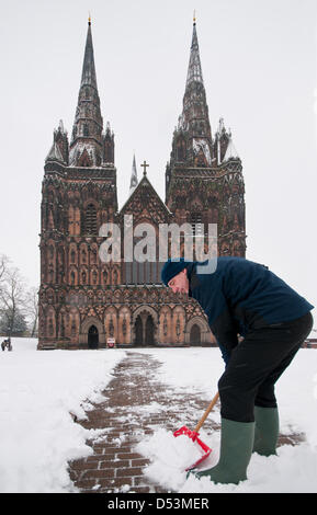 Lichfield, Staffordshire, UK. 23rd March 2013. Head Verger Chris Craddock clearing snow in front of Lichfield Cathedral - Stock Image