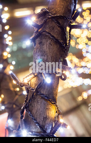 Christmas lights gold and white wrapped around tree with bokeh background - Stock Image