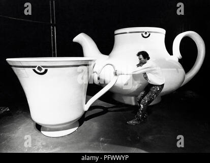 Garden Festival Wales 1992. Model maker Thurston Watson with giant teapot & cup created for the Hoover pavilion. - Stock Image