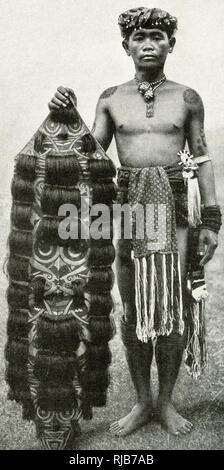 Young Kenyah man with his shield, Borneo, SE Asia (then part of the British Empire). It has a stylised face painted on it, and is decorated with human hair from his victims. - Stock Image