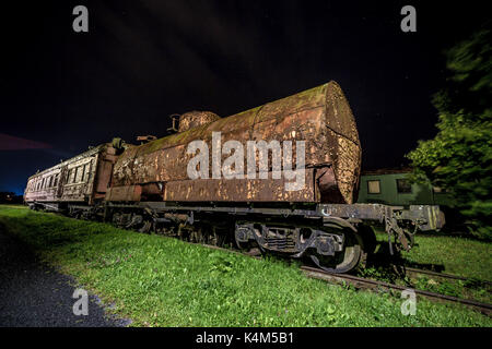 Decayed locomotive car at night - Stock Image