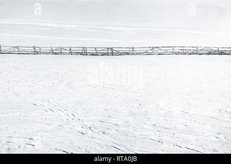 Wooden fence in the countryside covered in snow in wintertime. Copy space for text. - Stock Image