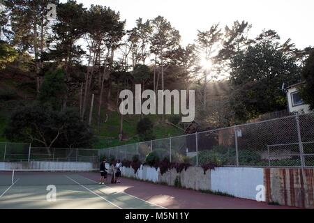 Two people prepare to play tennis under sunrays through the trees in San Francisco. - Stock Image