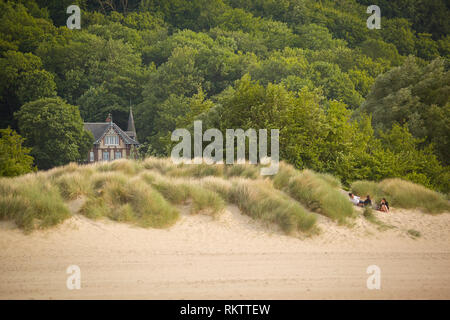 A group of people picnic on the sand dunes by the beach at Honfleur, Le Plage Du Butin, Normandy, France. - Stock Image