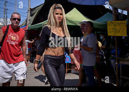Woman wearing blond hair extensions and very sexy clothing in a Pattaya street scene. - Stock Image