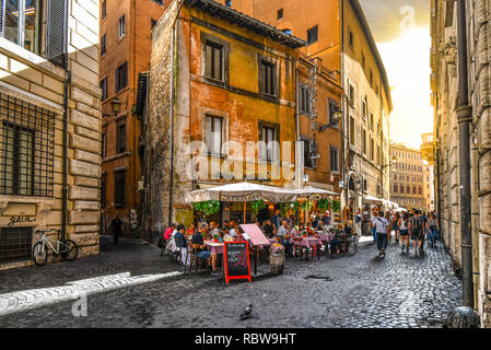 Tourists and locals enjoy a late afternoon shopping and dining at a sidewalk cafe patio on a narrow side street in the historic center of Rome, Italy - Stock Image