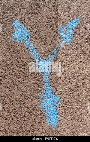Spray painted markings left on road by contractors to indicate positioning of water utilities. - Stock Image