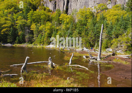 Partial view of Avalanche Lake, Adirondack region, New York State, USA. Two hikers are resting, seated on a log on the right side of the image. - Stock Image