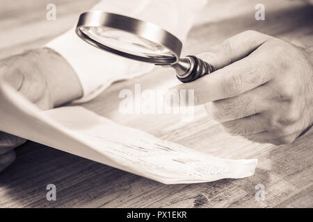 Businessman Checking His Documents With A Magnifying Glass, Monochrome Colors - Stock Image