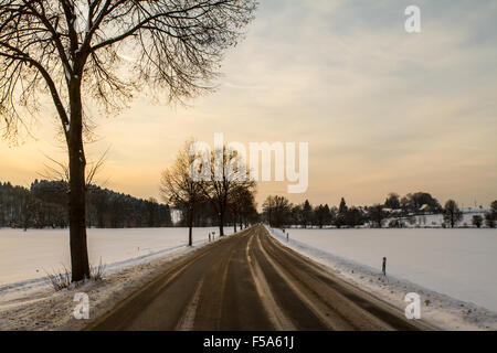 Road in the snow at sunset - Stock Image