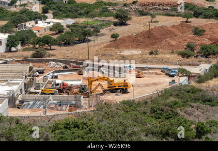 Plaka, Crete, Greece. June 2019. Construction work being carried out behind the coastal village of Plaka. Building new homes and apartments. - Stock Image