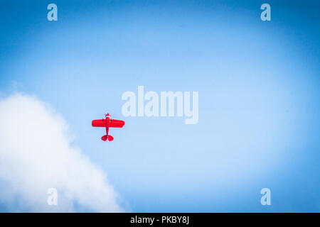Red propeller plane flying upwards on a blue heaven with white clouds - Stock Image