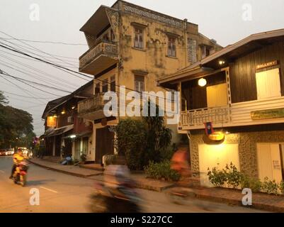 Scooters riding past old buildings in Luang Prabang Laos - Stock Image