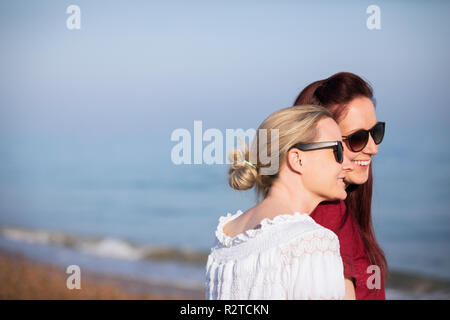 Affectionate lesbian couple on sunny beach - Stock Image