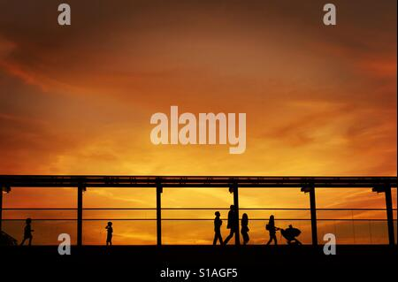 Silhouettes of a family on a bridge at sunset - Stock Image