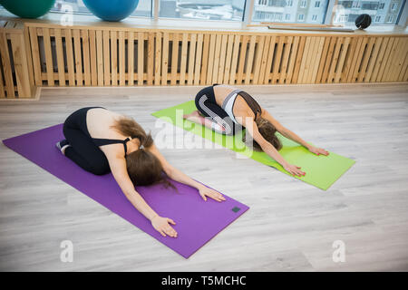 Young women doing yoga in the studio. Bend to the floor - Stock Image