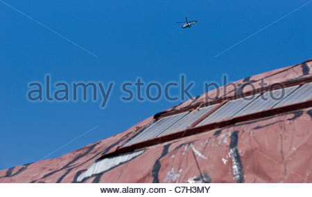 Galvanized steel sheet metal roof with asphalt tar coating painted over seams plus solar panels - Stock Image