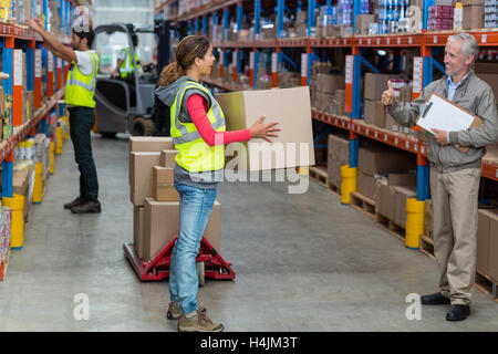 Warehouse manager showing thumbs up to female worker while carrying cardboard boxes - Stock Image