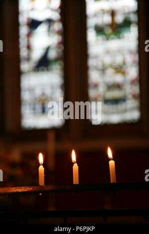Three candles burning as a remembrance ahead of stained glass windows in a small church in Dublin, Ireland, Europe. - Stock Image