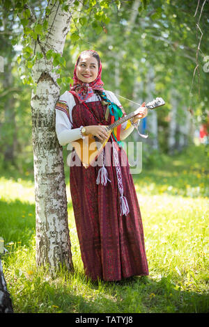 Young thoughtful woman in traditional russian clothes standing in the forest and holding balalaika, vertical shot - Stock Image
